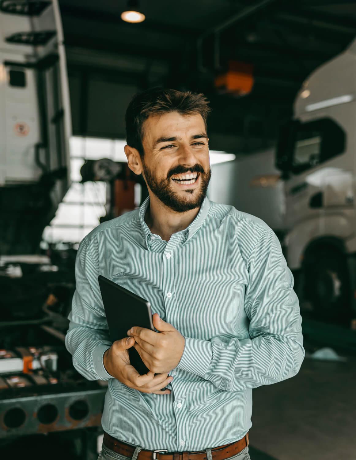 personne souriant et tenant un iPad dans un hangar à véhicule